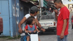 Man with two children on motorcycle talking in the streets of city Stock Footage