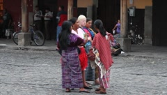 Women with albino woman in native dress along busy Guatemalan street Stock Footage