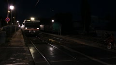 Passenger train aproaches and passes by in the night Stock Footage