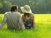 Couple sitting on meadow and looking at the landscape Stock Footage