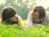 Happy couple lying on a meadow and talking Stock Footage