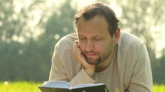Young man lying on the grass and reading book, dolly shot Stock Footage