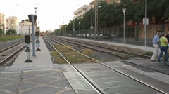 Two cyclists crossing the rails at a grade crossing Stock Footage