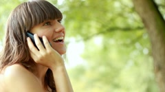 Young attractive woman talking on mobile phone in the park - stock footage