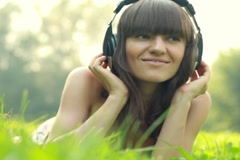 Woman with headphones listen to the music in the park Stock Footage