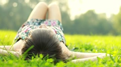 Portrait of young happy beautiful woman lying on grass, dolly shot - stock footage