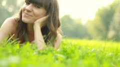 Portrait of young happy beautiful woman lying on the grass, dolly shot - stock footage