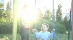 Mom shakes her little boy on a swing - stock footage