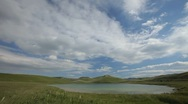 Stock Video Footage of Small lake on a grassy glade with big cluds moving fast casting shadows