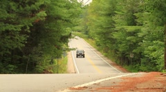 Jeep driving towards camera on rural road. - stock footage