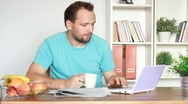 Portrait of young man drinking coffee, tea and working on laptop HD Stock Footage
