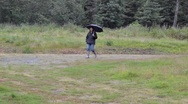 Sad woman walking in the rain Stock Footage