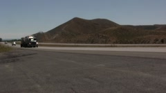 Semi and cars driving on a desert highway with mountains Stock Footage