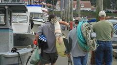Fishermen, carrying gear on dock Stock Footage