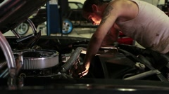 Man working on the engine of a classic car in a shop - stock footage