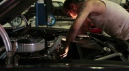 Man working on the engine of a classic car in a shop Stock Footage