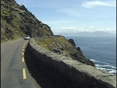 Stock Video Footage of Dingle Peninsula, Ireland, Car on Road overlooking the ocean.