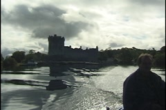 Boat on Lakes of Killarney, Ireland, with Ross Castle in Background Stock Footage