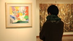 Asian woman watching paintings at a gallery in Korea Stock Footage