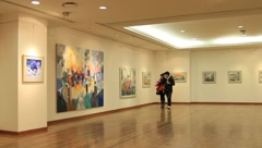 Young couple watching paintings at a gallery in Korea - stock footage
