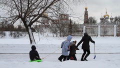 Mother and children playing with a snow sled at the park of Novodevichy Monaster Stock Footage