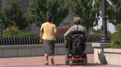 Old man in a Jazzy Cart Wheel Chair walk to the office Stock Footage