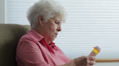 Senior woman at home reading prescription bottle Stock Footage