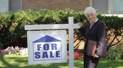 Real estate agent in front of house by for sale sign - stock footage