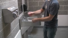 Drying hands in a public bathroom Stock Footage
