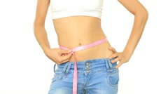 Stock Video Footage of Slim woman in jeans measuring her belly with measuring tape, isolated on white