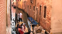 A gondolier rows a gondola on a narrow canal in Venice Italy Stock Footage