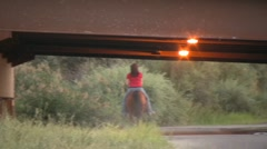 A woman riding beauty the horse under a bridge Stock Footage