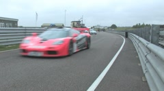 McLaren F1 leading supercars on to track Stock Footage
