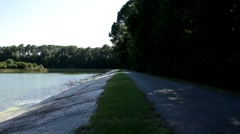 Walking trail at a city park by a pond Stock Footage