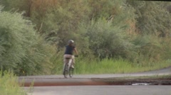 Woman riding a bike on the parkway Stock Footage