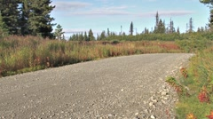 Minivan comes around corner on gravel road Stock Footage