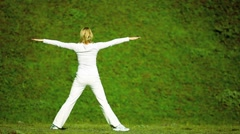 Female in White Relaxing with  Yoga Outdoors Stock Footage