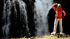 Young Hiker Viewing a Cascading Waterfall Stock Footage