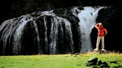 Young Hiker Viewing a Cascading Waterfall - stock footage