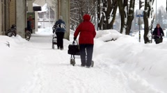 old woman walking with push cart in the snow - stock footage