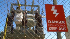 Electrical worker on substation with danger sign Stock Footage