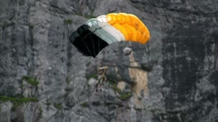 A man paraglides through a mountain pass near a waterfall. Stock Footage