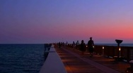 People walking Dan Russell Pier at sunset in Panama City Beach Stock Footage