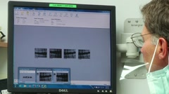 Dentist points to X-ray on computer screen Stock Footage