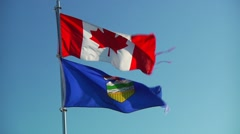 Zoom out of Canadian and Alberta flags waving in wind Stock Footage