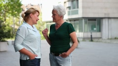 Two women chatting in the city Stock Footage