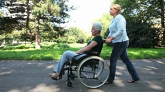elderly woman in wheelchair in park - stock footage