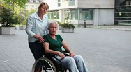 Woman in wheelchair discussing with nurse Stock Footage