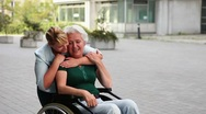 Woman in wheelchair and nurse holding thumbs up Stock Footage