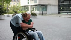 nurse hugging woman in wheelchair - stock footage